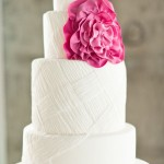 white wedding cake with pink flower