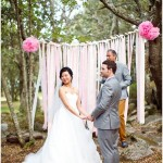 woodland wedding ceremony with pastel pink decorations and backdrop