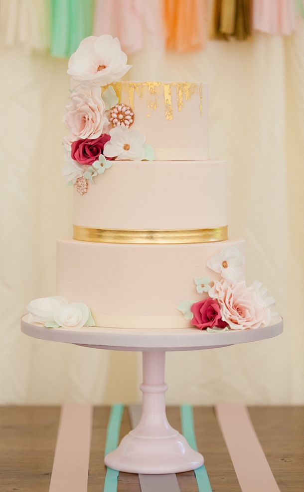 Pink and gold wedding cake with flowers