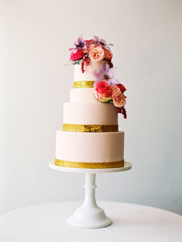 gold and pink wedding cake with fresh flowers