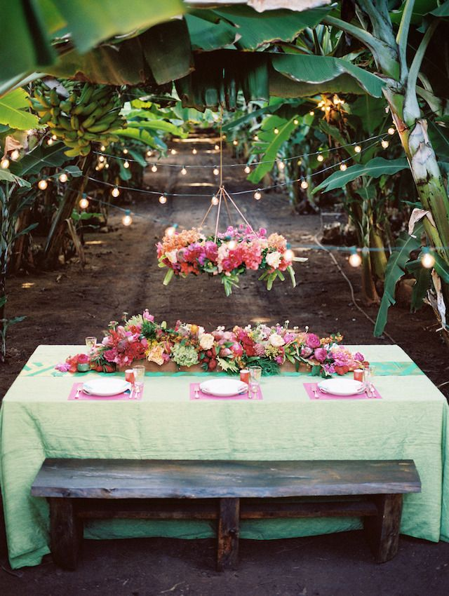 A colorful and tropical banana grove wedding photographed by Jonathan Canlas in Hawaii with a tropical flower chandelier.