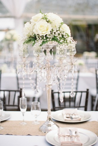 A classic crystal candelabra with white roses | Photography: Bob Care - careweddings.com/