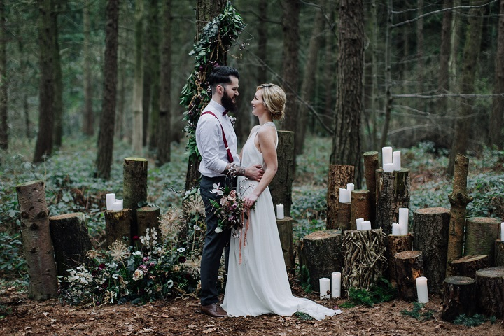 Wedding altar decorated with stacked logs with candles on tops at various heights - Beautiful woodland wedding styled shoot with cranberry red accents | fabmood.com #weddinginspiration #styledshoot #woodland #weddingideas #autumnwedding #cranberrywedding #weddingceremony #woodlandceremony
