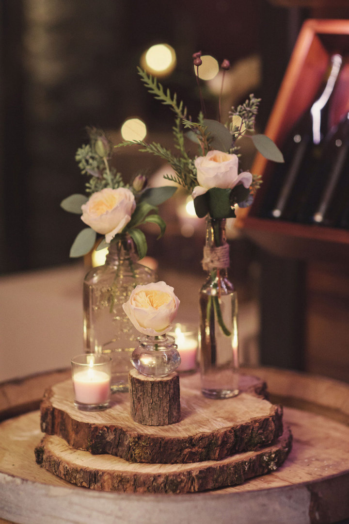 Roses filled in brown bottles with twine wrapped on wooden slice as rustic wedding centerpice,rustic centerieces,bottle centerpieces ,wine bottle centerpieces,wooden slice centerpieces #weddingcenterpieces #rusticweddingcenterpieces