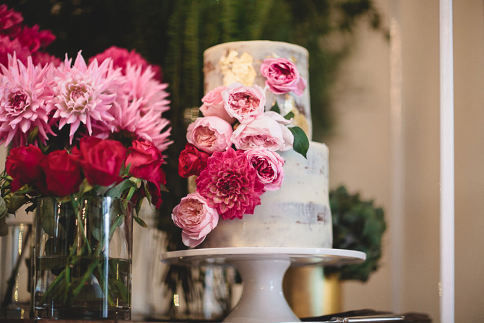 Semi naked wedding cake with gold foil and tiopped with vibrant flowers