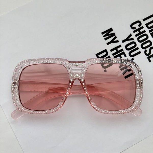 Trendy crystal star embossed on light pink sunglasses.
