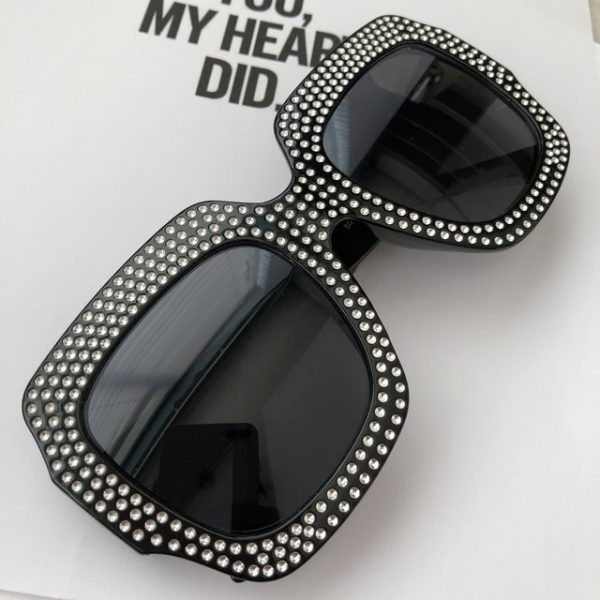 Trendy crystal embossed on black sunglasses with black tint.
