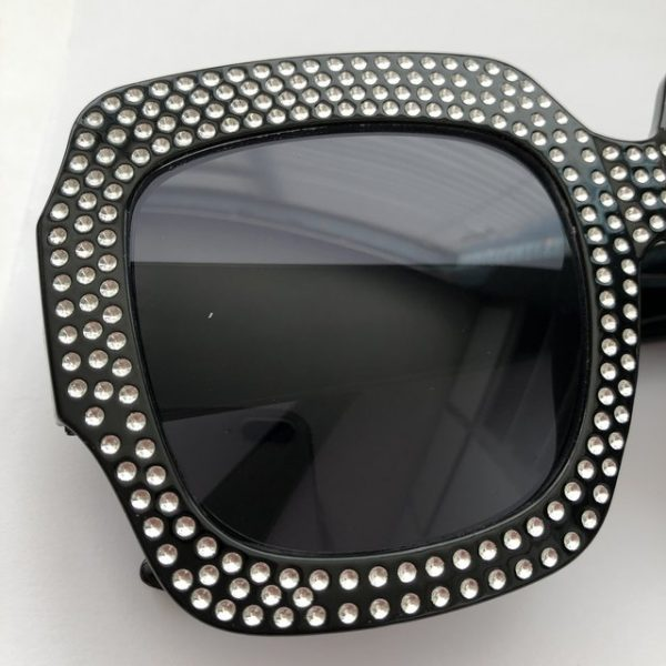 Trendy crystal embossed on black sunglasses with black tint.