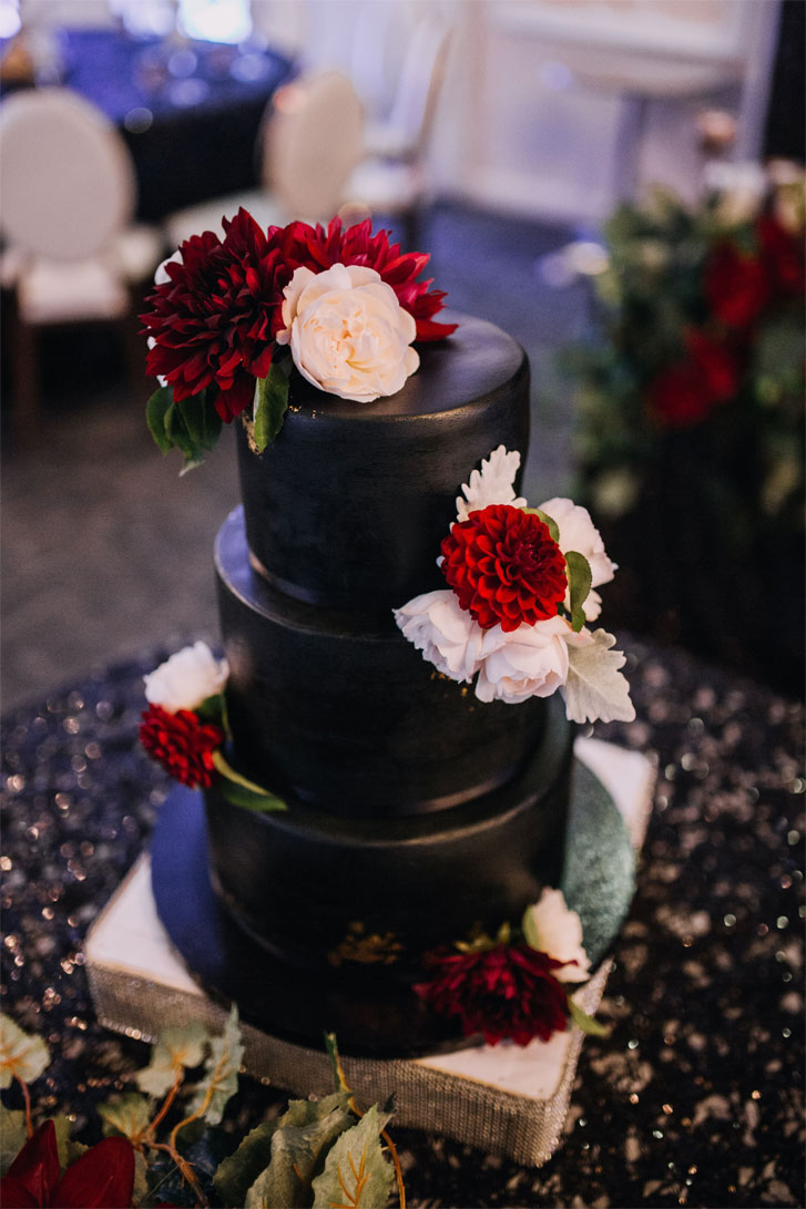 Three tier black wedding cake adorned with white and red flowers #weddingcake