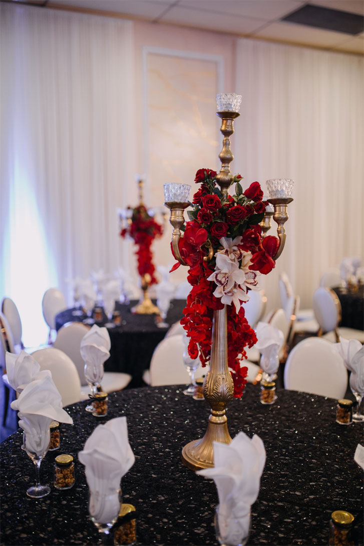 Candles on Gold tall wedding centerpiece adorned with red floral for a gothic style wedding