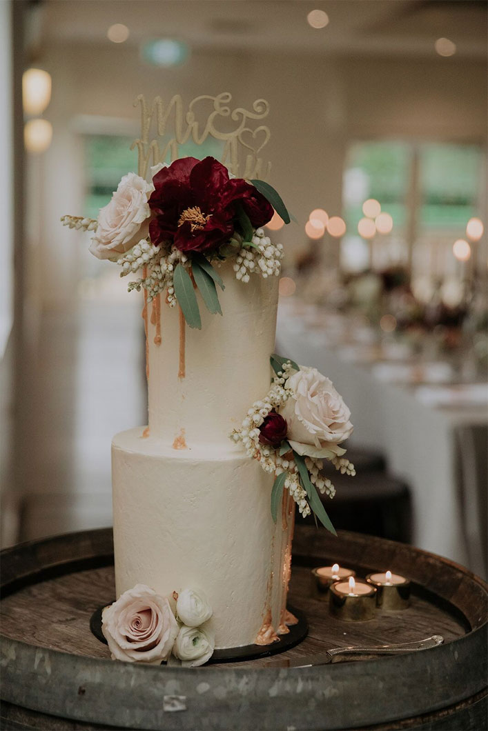 Gorgeous two tier wedding cake adorned with blush and burgundy flowers -Intimate Wedding With A Touch Of A Moody Palette For A Destination Wedding