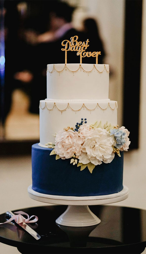 This stunning three-tiered white and navy blue wedding cake is positively drowning in pretty blush and blue sugar flowers.