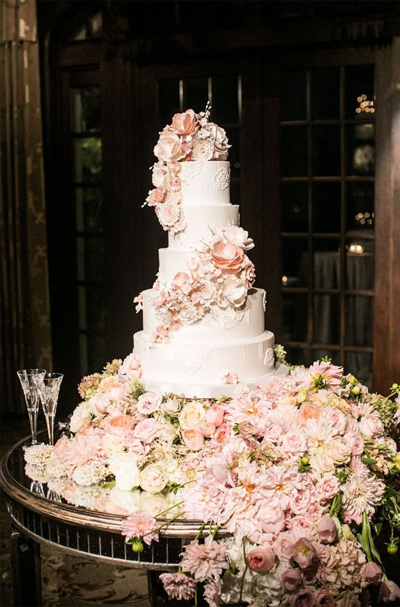 wedding cake dripping in white and blush flowers - The prettiest floral wedding cakes for any season #weddingcake