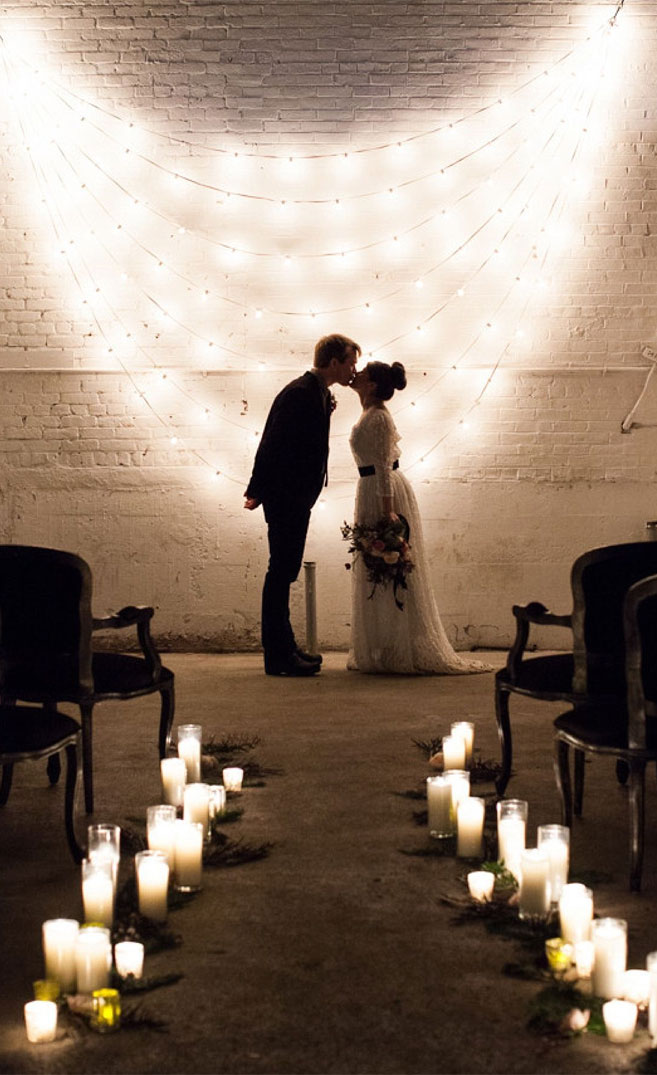 Fairy lights hanging on the wall as wedding altar backdrops and lots of candle decorates wedding aisle for industrial wedding ceremony setting