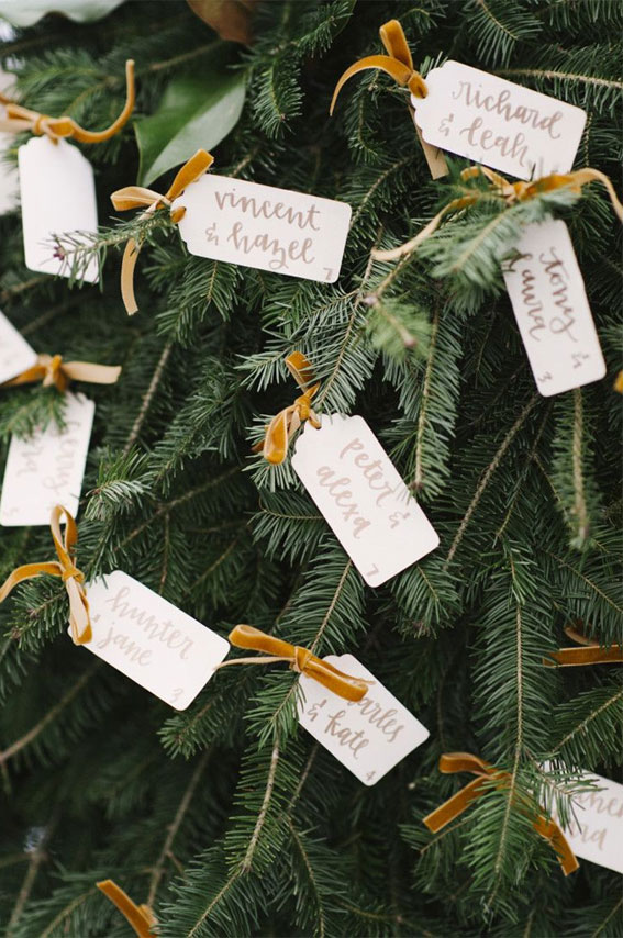 Simple white tag as escort cards hang on Christmas tree , winter wedding ideas