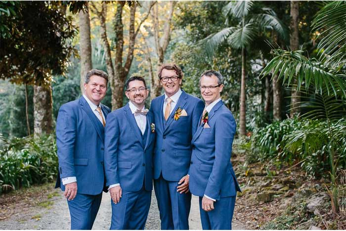 groom and groomsmen in blue with bold boutonnieres