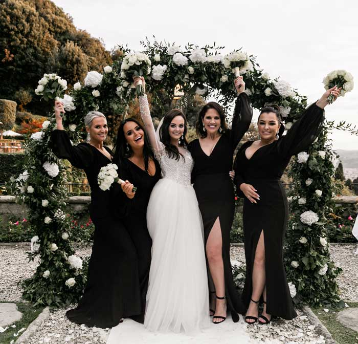 black bridesmaid dresses, greenery wedding arch
