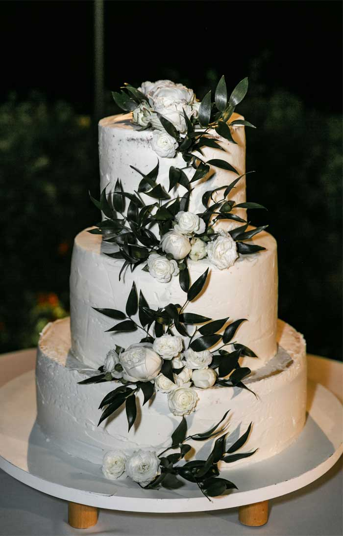 white three tier wedding cake with greenery and white flowers, wedding cake